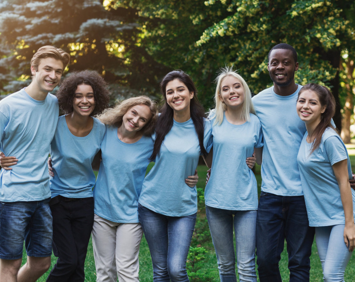 Group of happy young diverse volunteers embracing at park